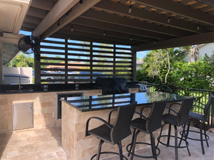 photo of the inside of a pergola with outdoor kitchen and chairs