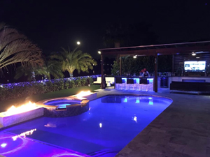 night-time image showcasing outdoor lighting inside and around a swimming pool
