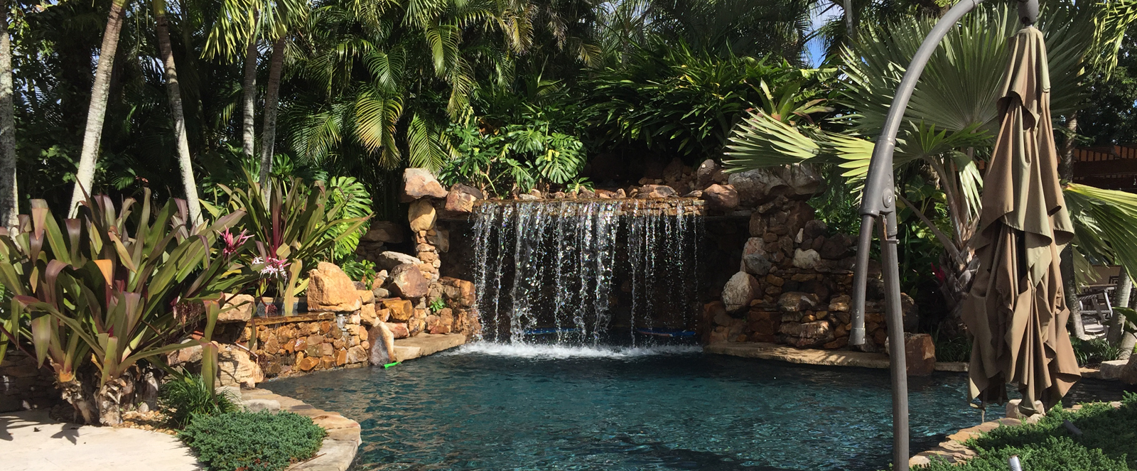 close shot of swimming pool with waterfall in background
